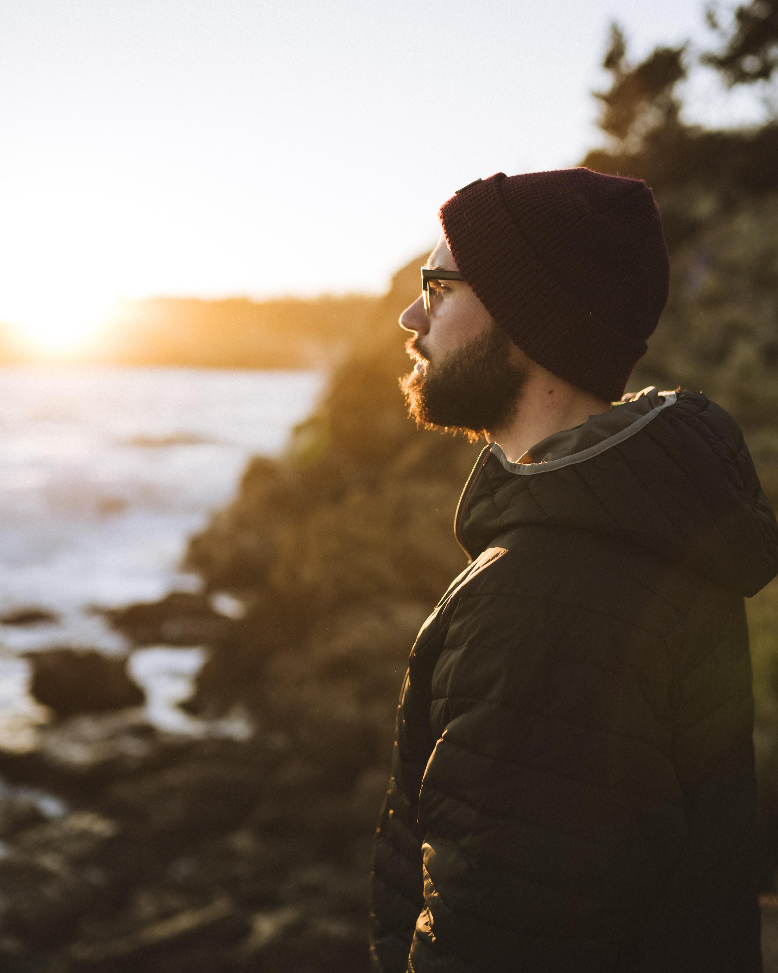 man facing sideways standing on sea rocks
