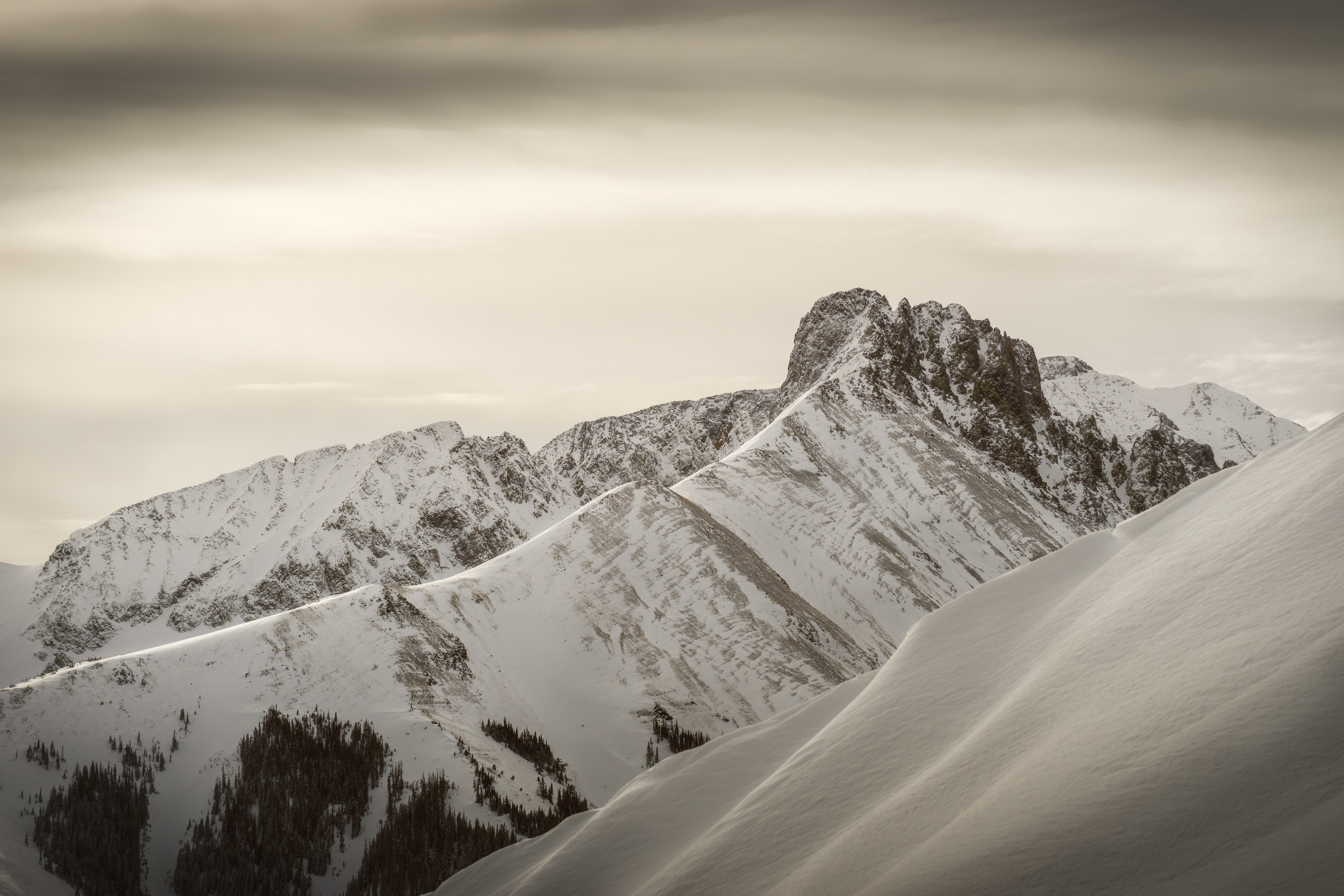 snow-covered mountains under gray clouds during daytime