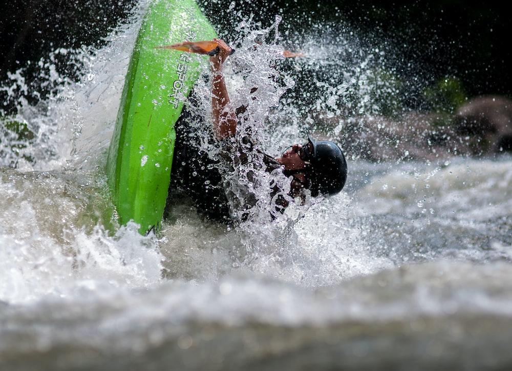 tilt-shift photography of man riding boat