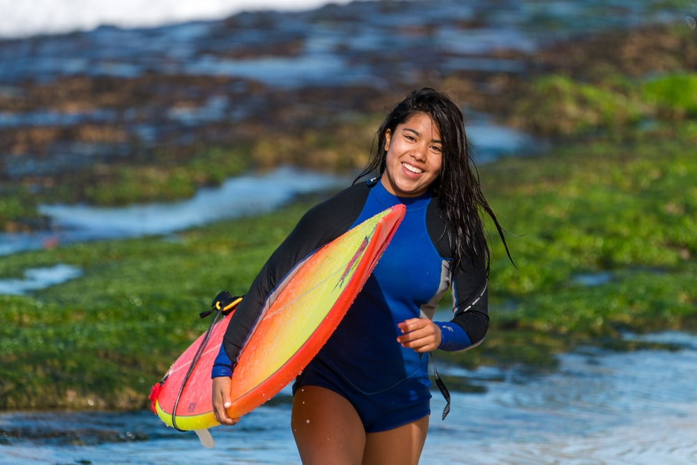 smiling woman carrying surfboard during daytime