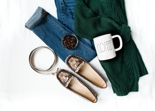 pair of brown leather flats and white ceramic mug