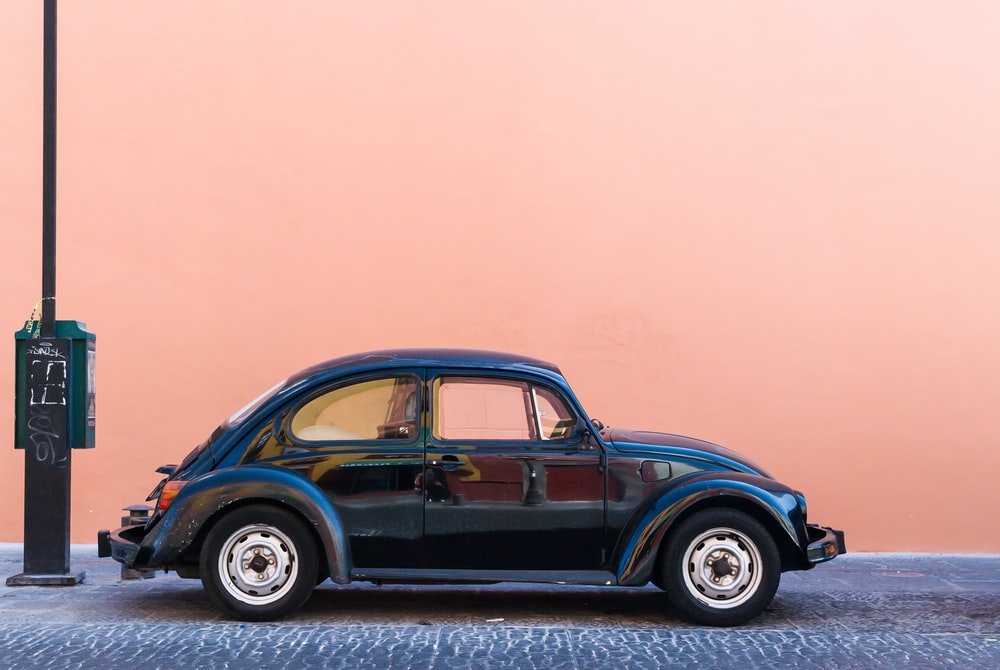 black Volkswagen Beetle beside beige wall