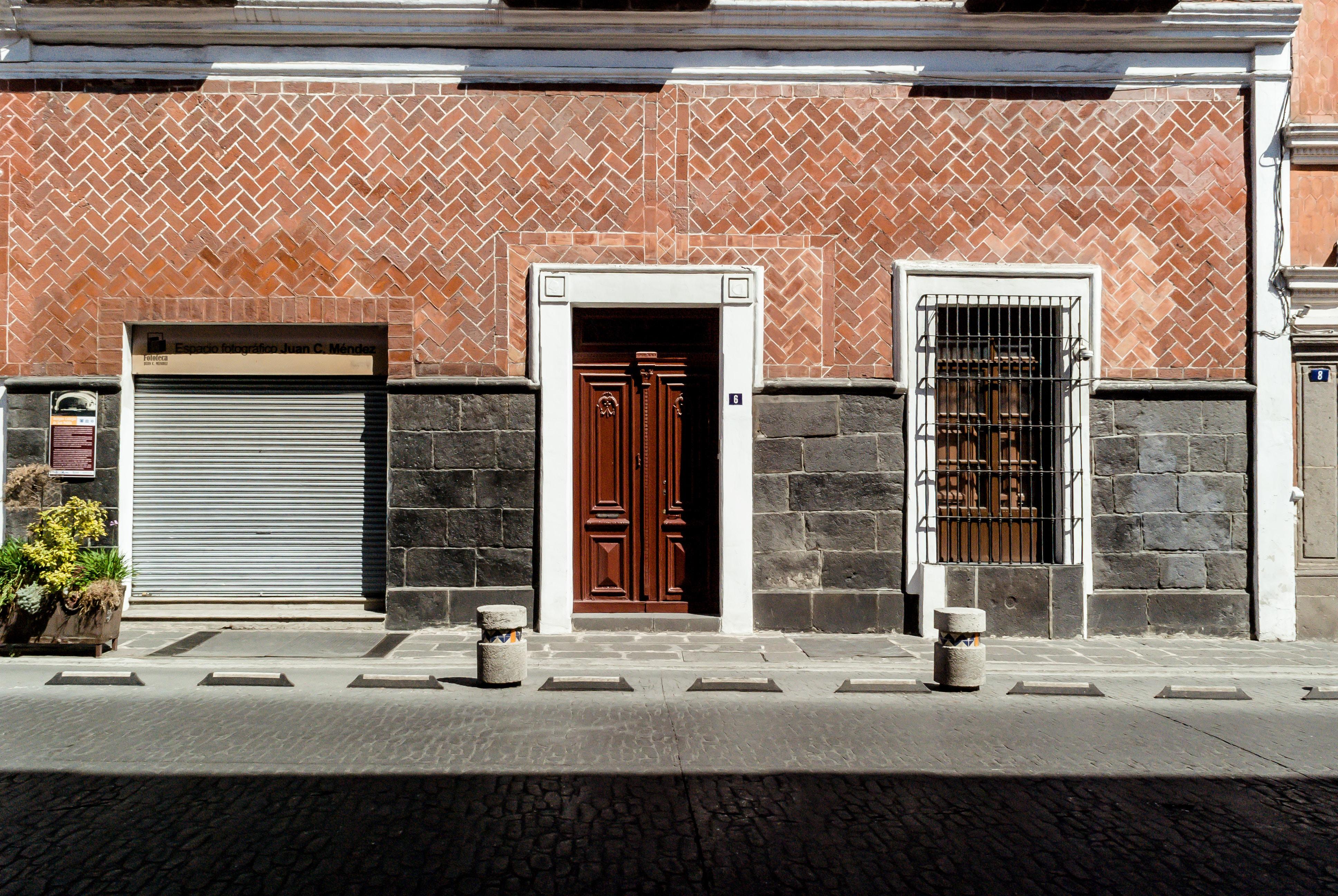 photo of closed brown wooden door beside roller shutter