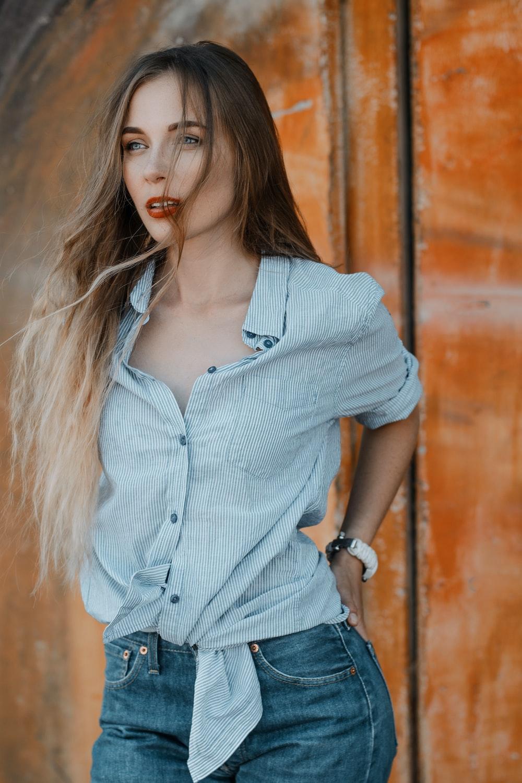 woman wearing dress shirt holding her gray denim bottom pocket