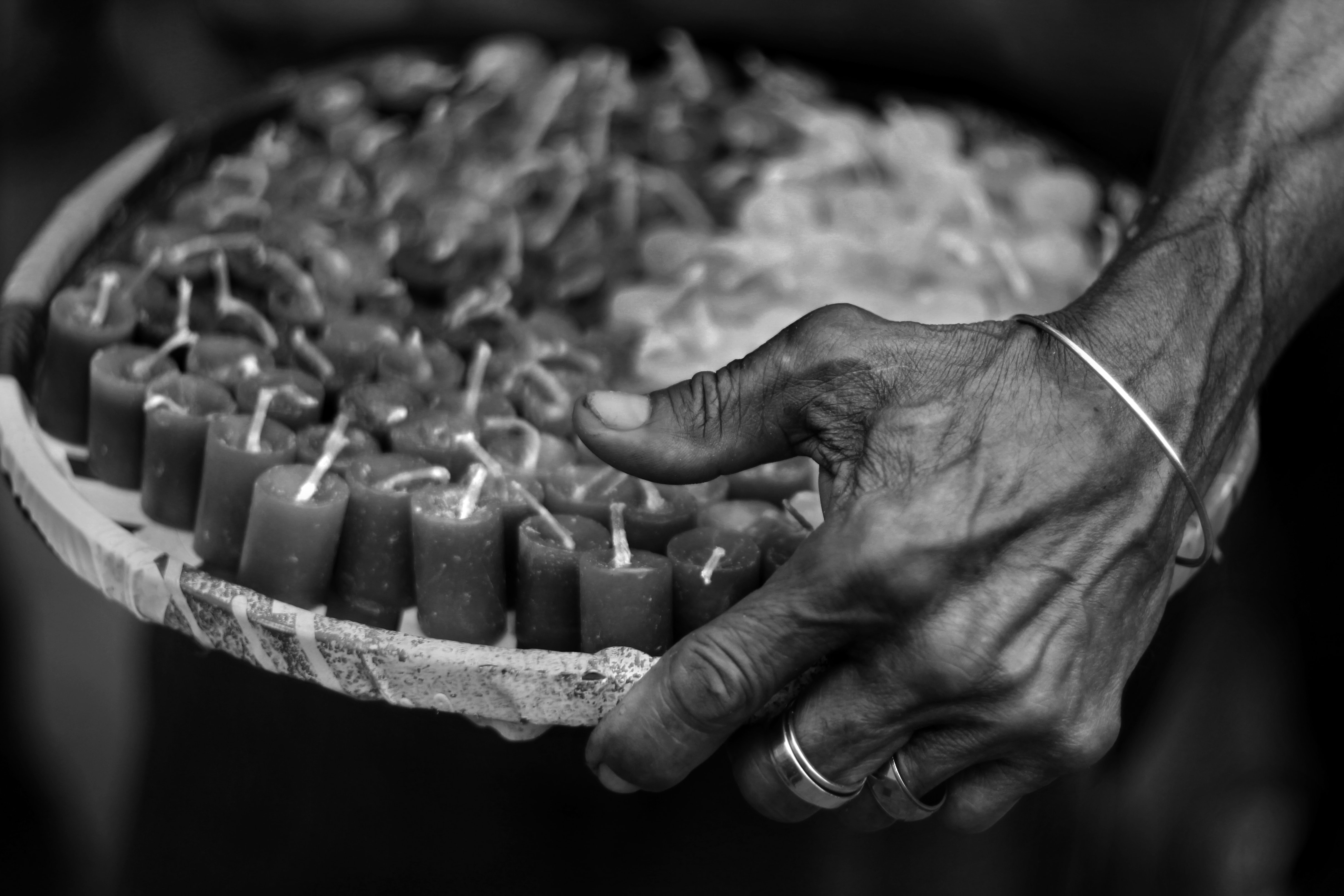 grayscale photography of person holding tray with candle lot