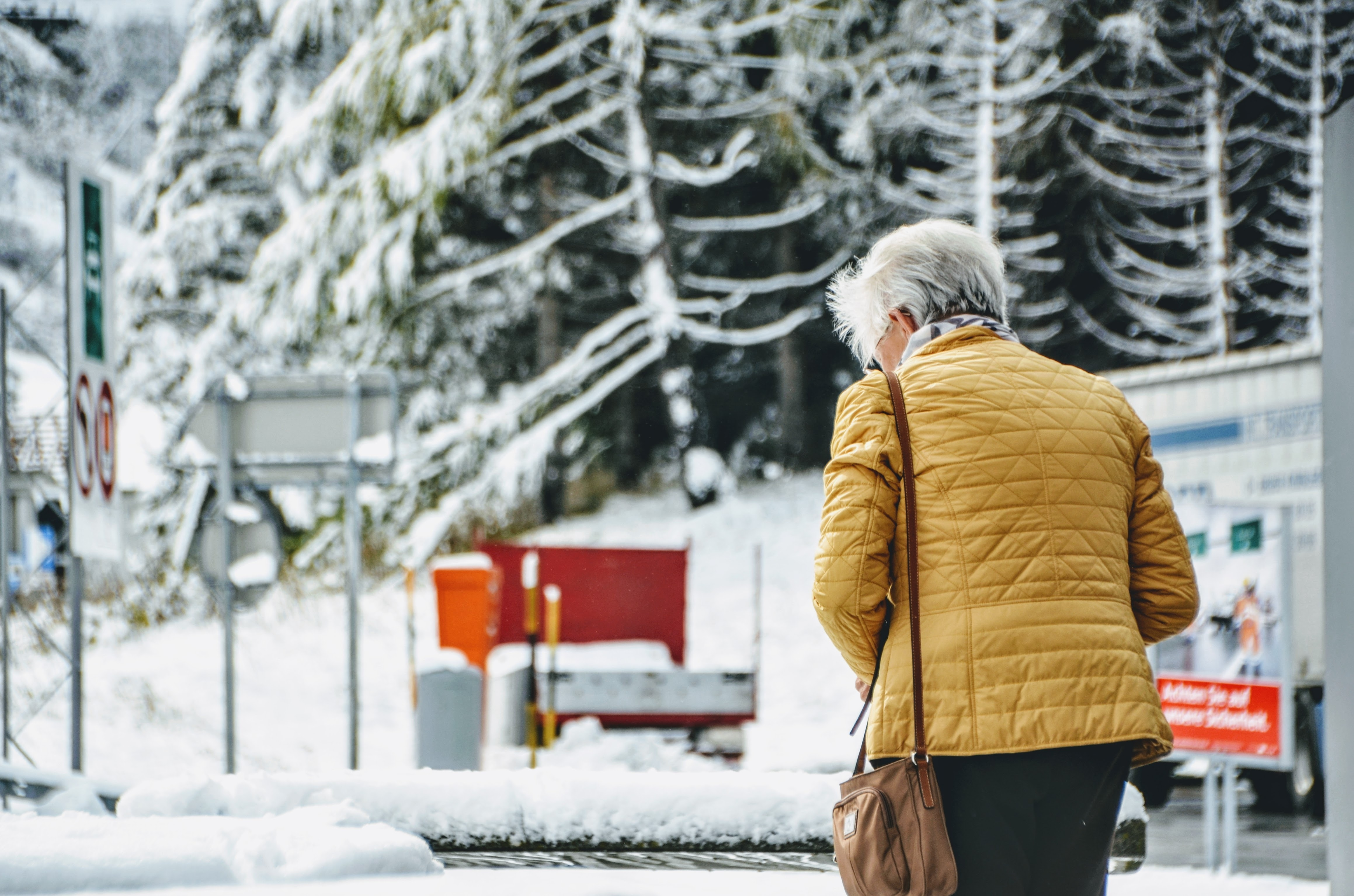 woman wearing quilted brown jacket and black bottoms walking on snowy ground