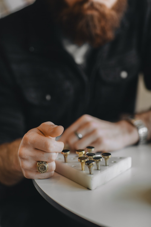 man looking on gold-colored taper gauge on desk