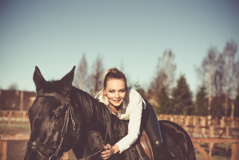 woman in white hoodie riding black horse