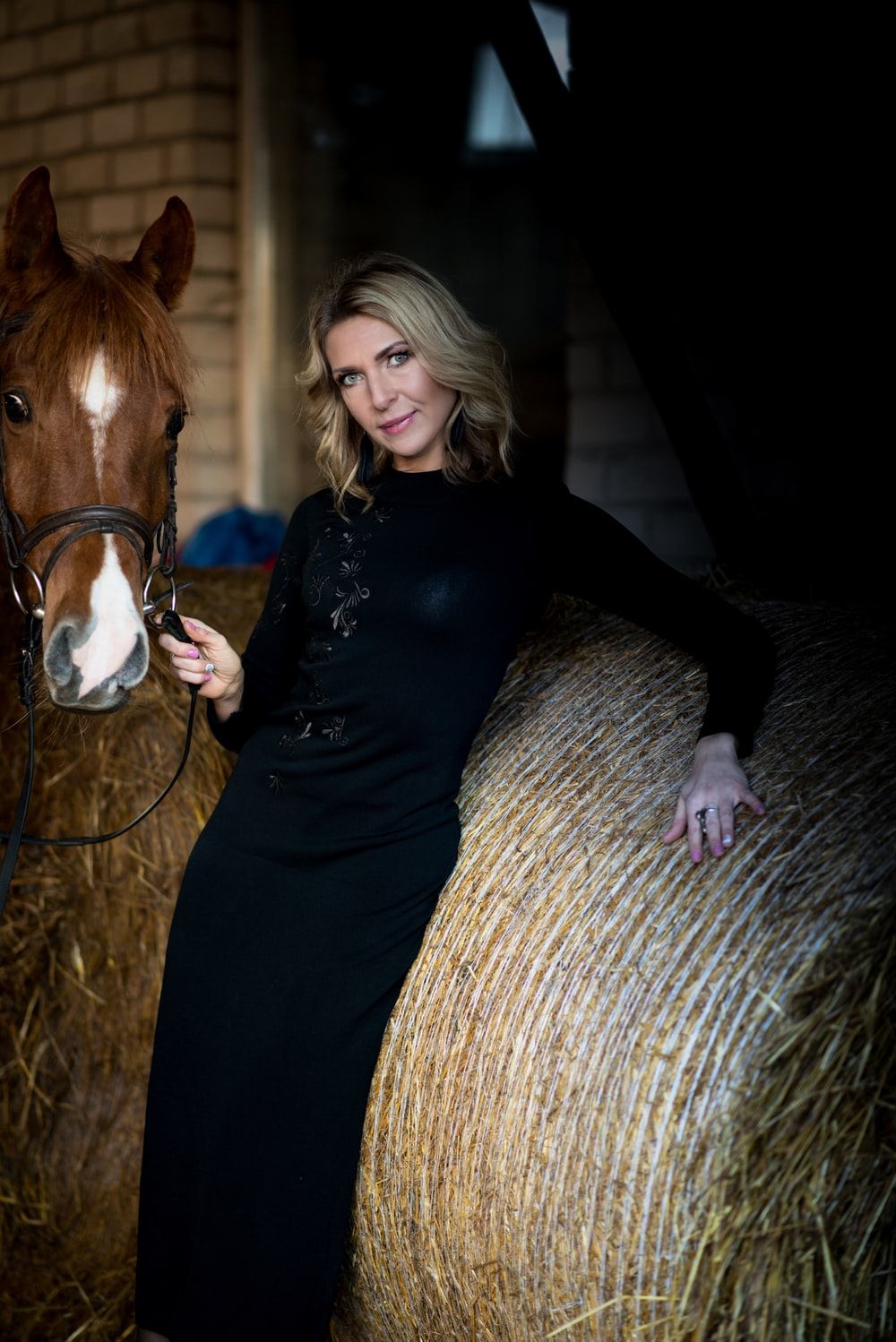 woman holding the horse strap while leaning on hay
