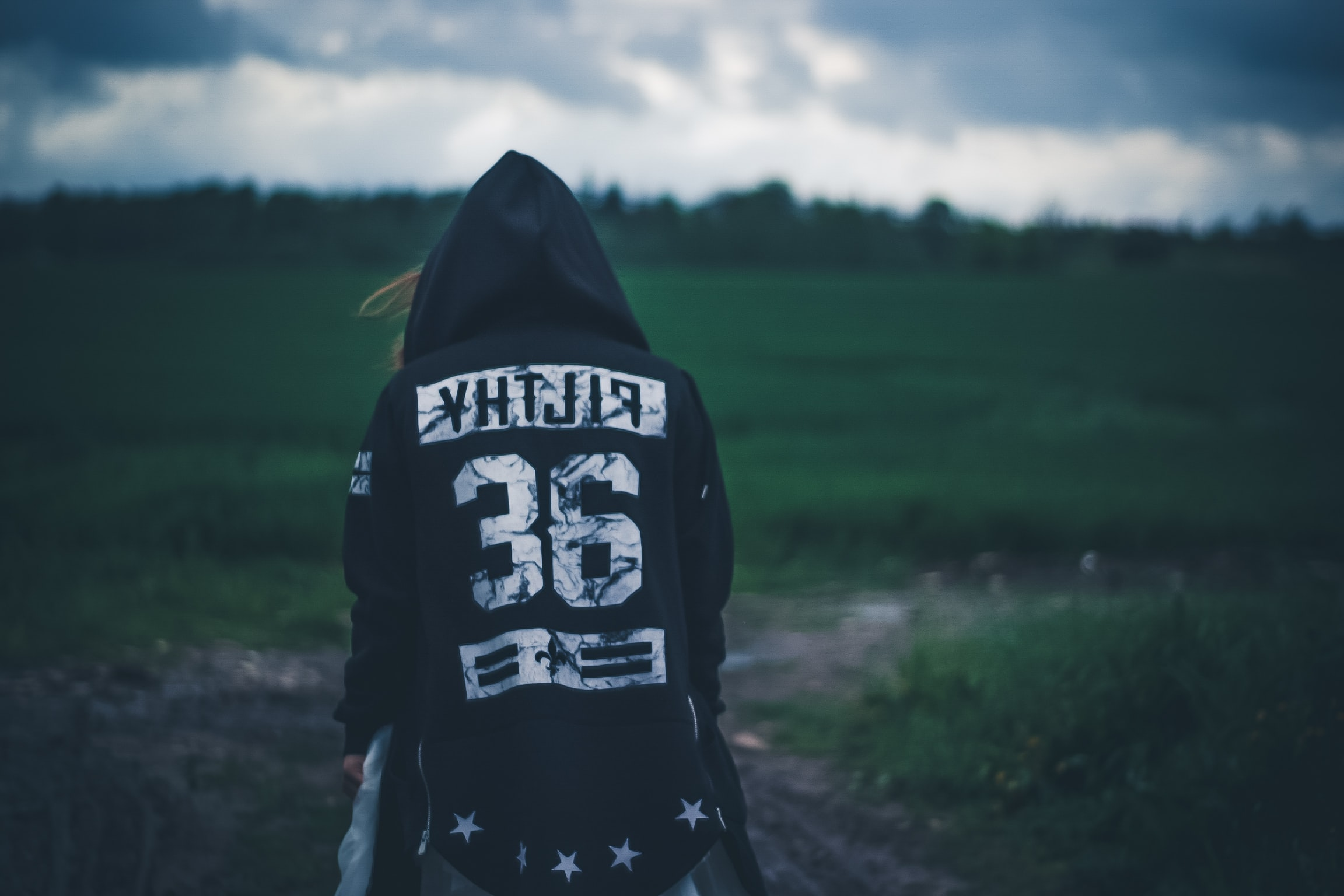 person wearing hooded jacket staring at grass