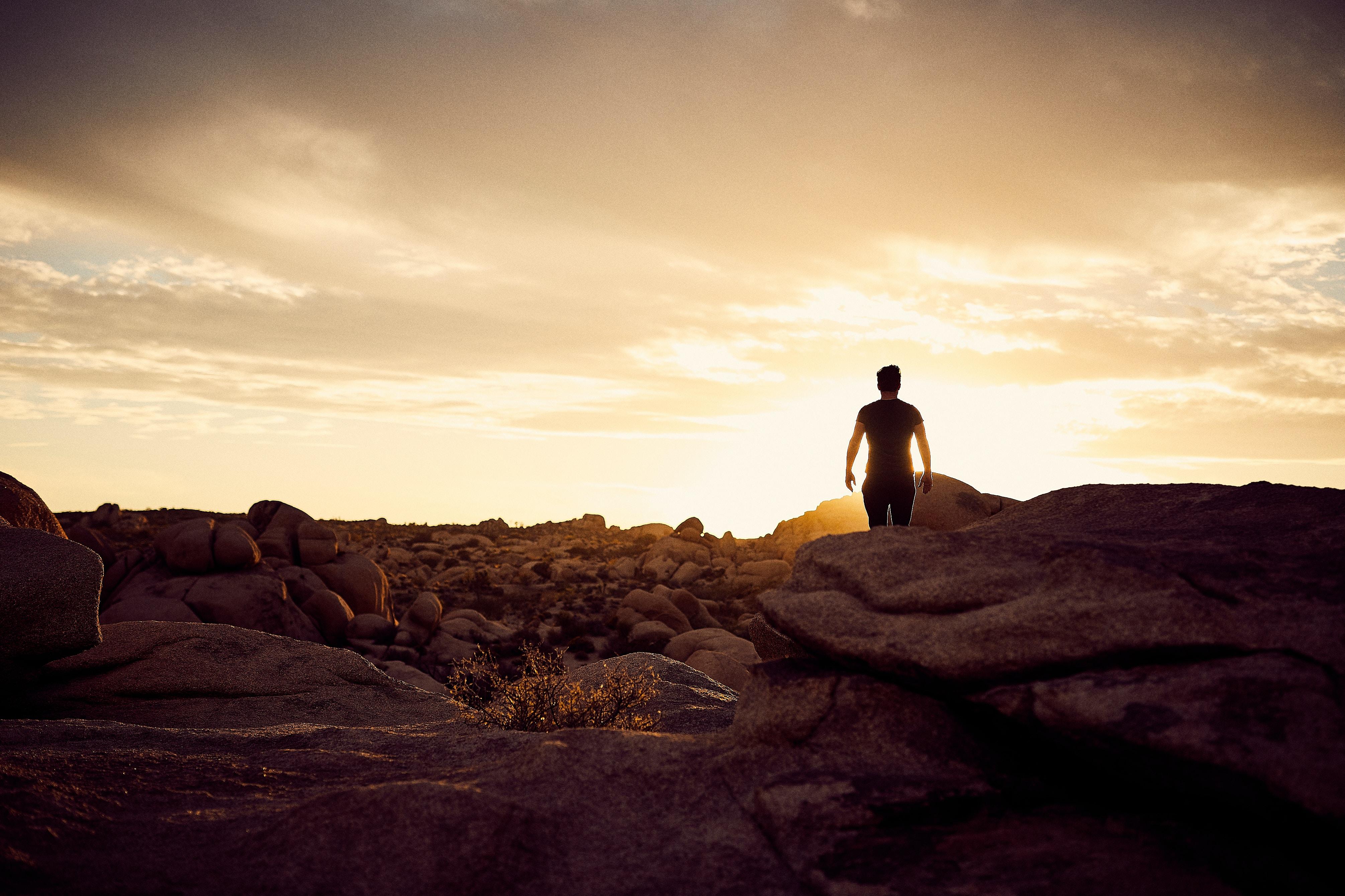 man walking on gray rocks under yellow sky during daytime