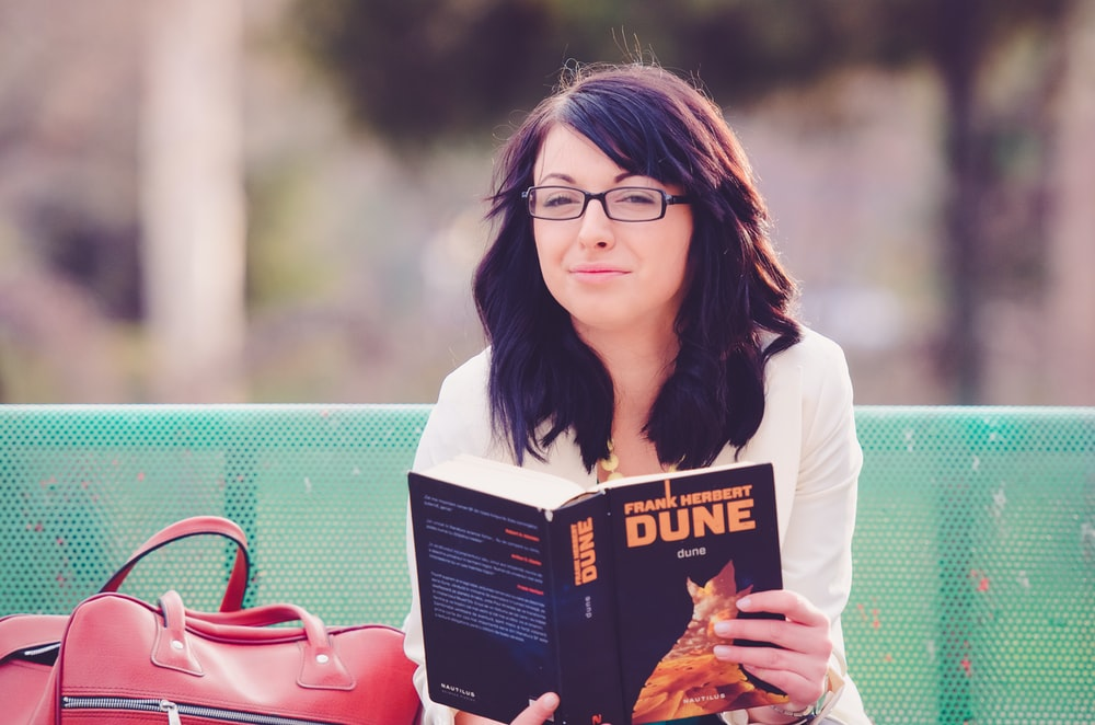 woman reading book while sitting on green bench