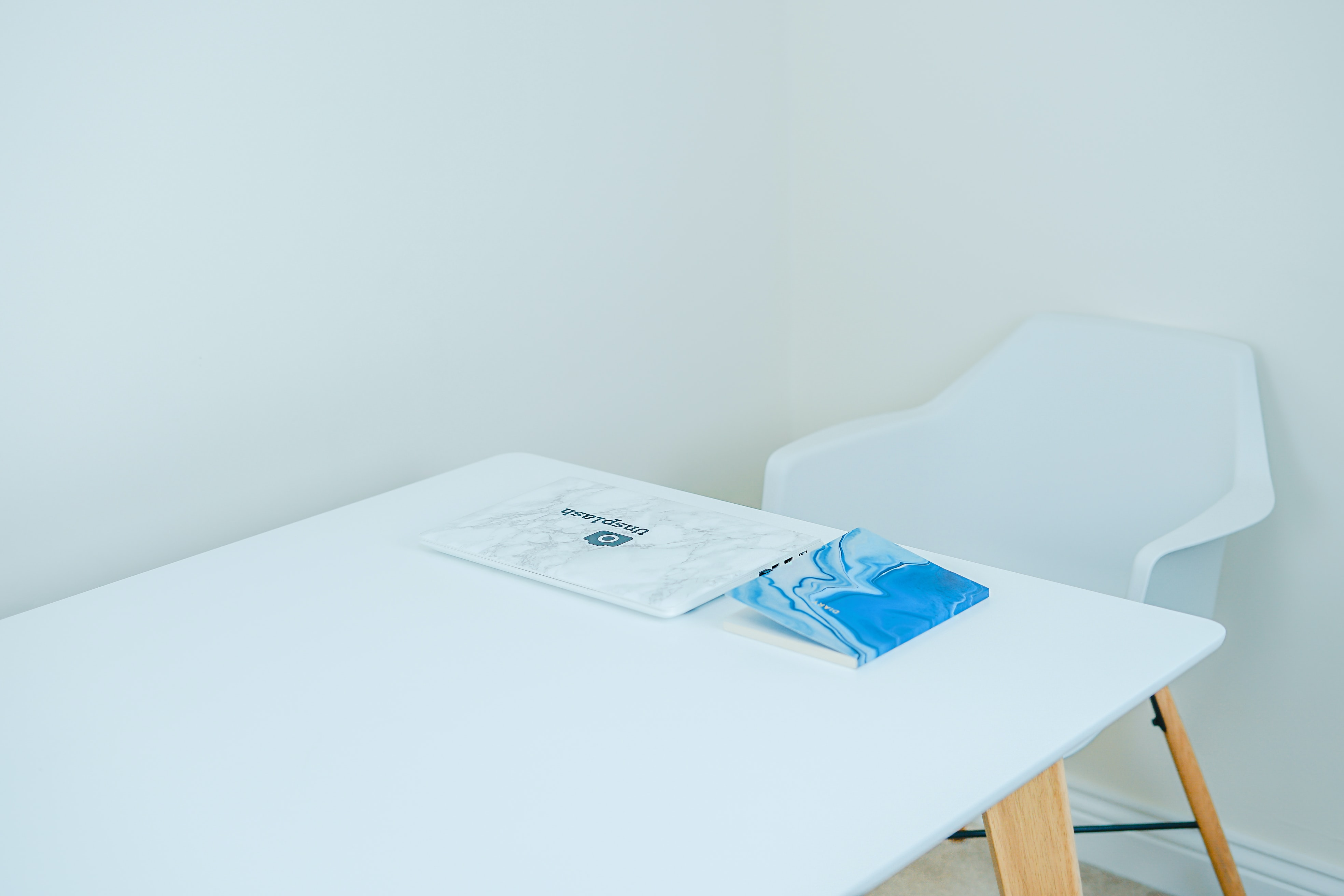 blue covered book on white table with armchair in front