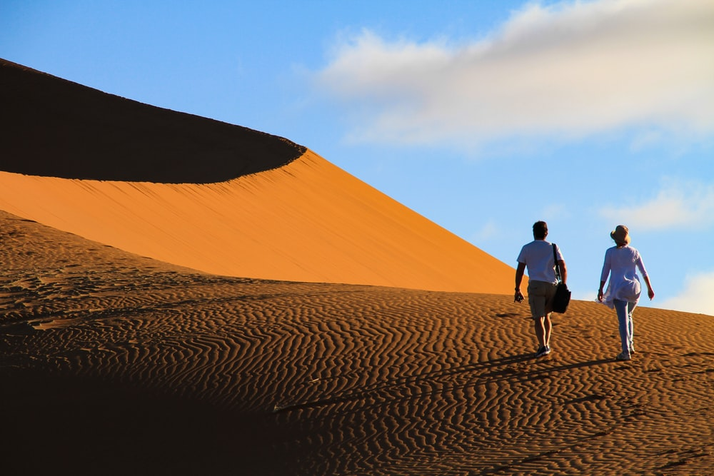 man and woman walking on desert
