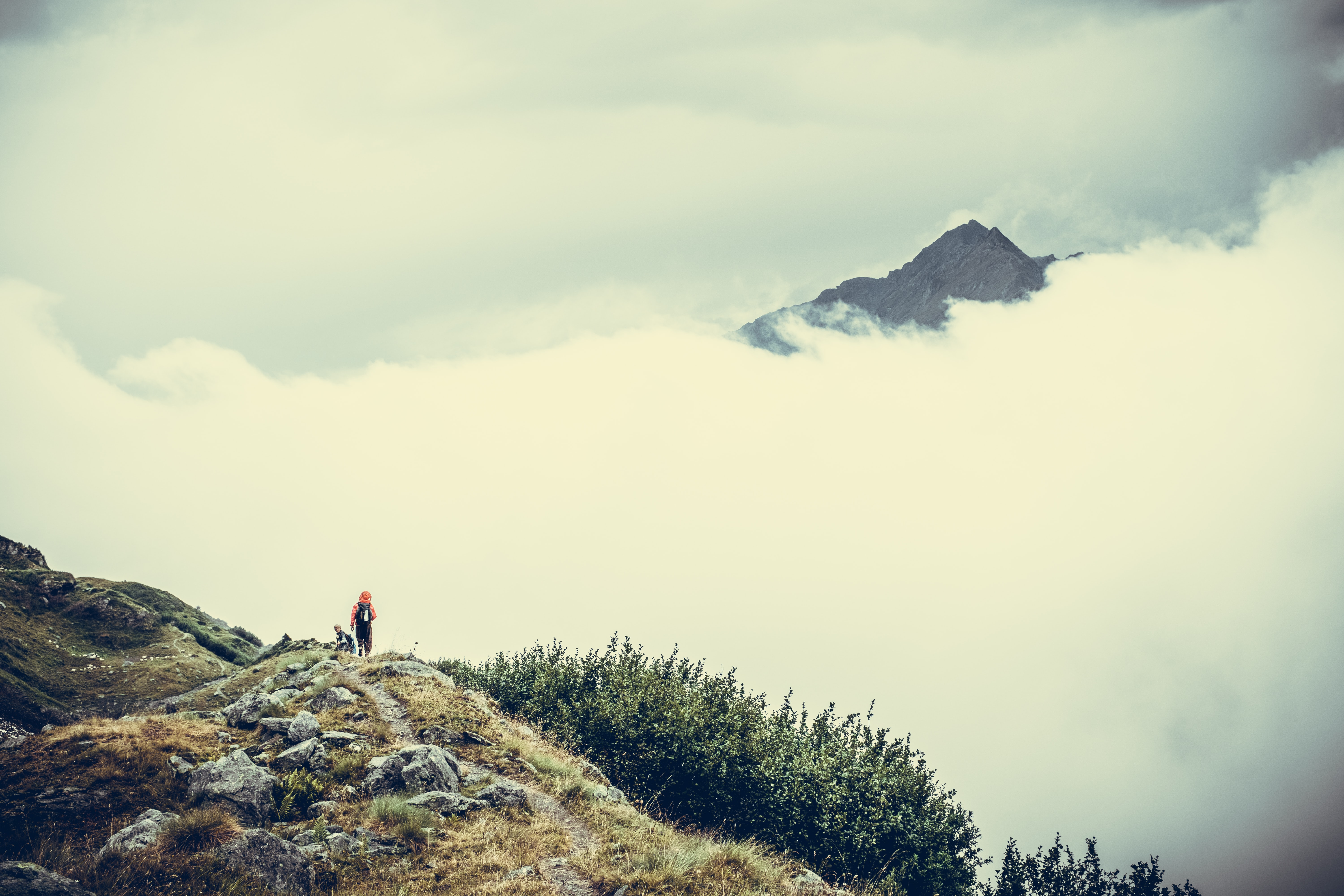 person on cliff watching sea of clouds