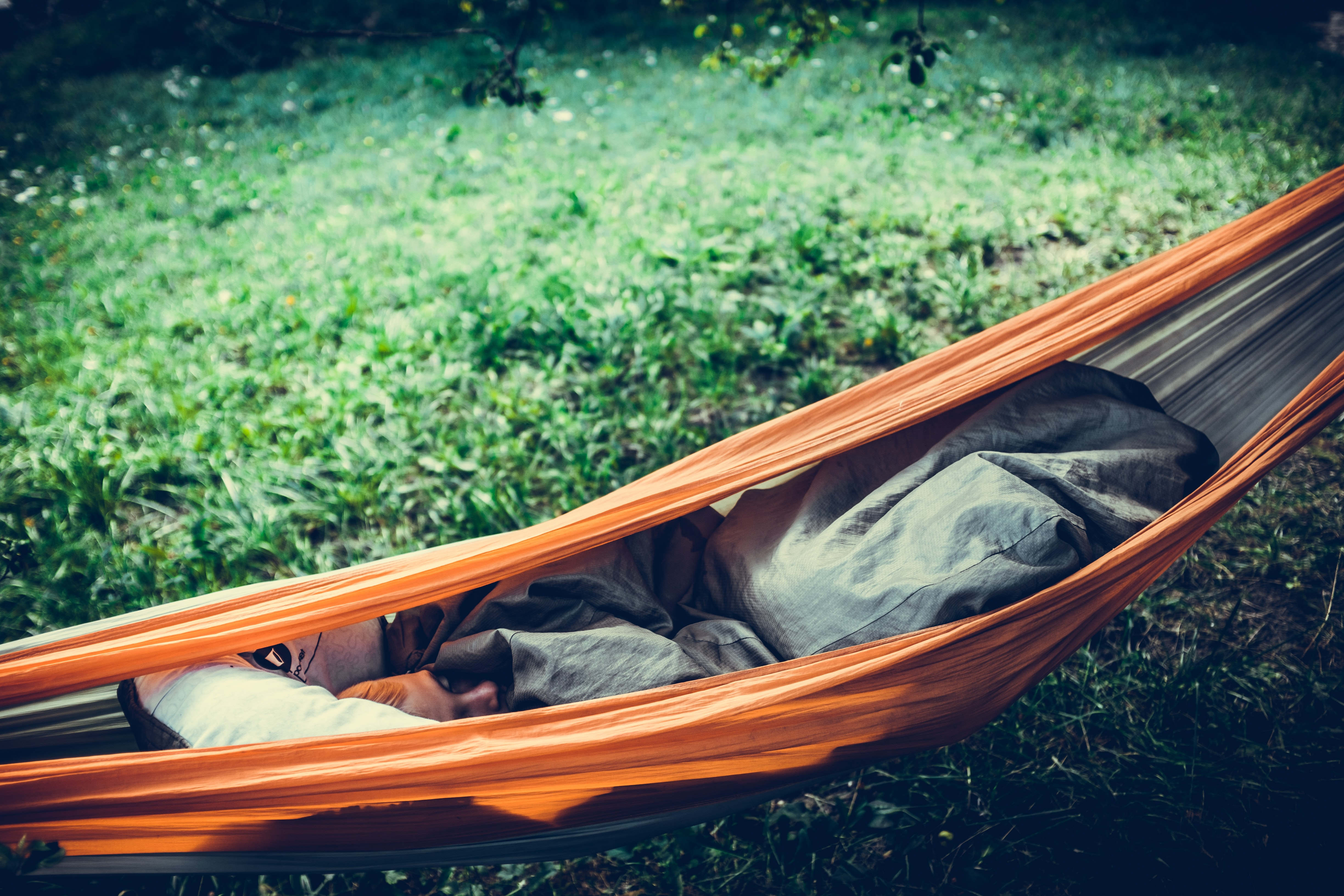 person lying on orange hammock outdoors