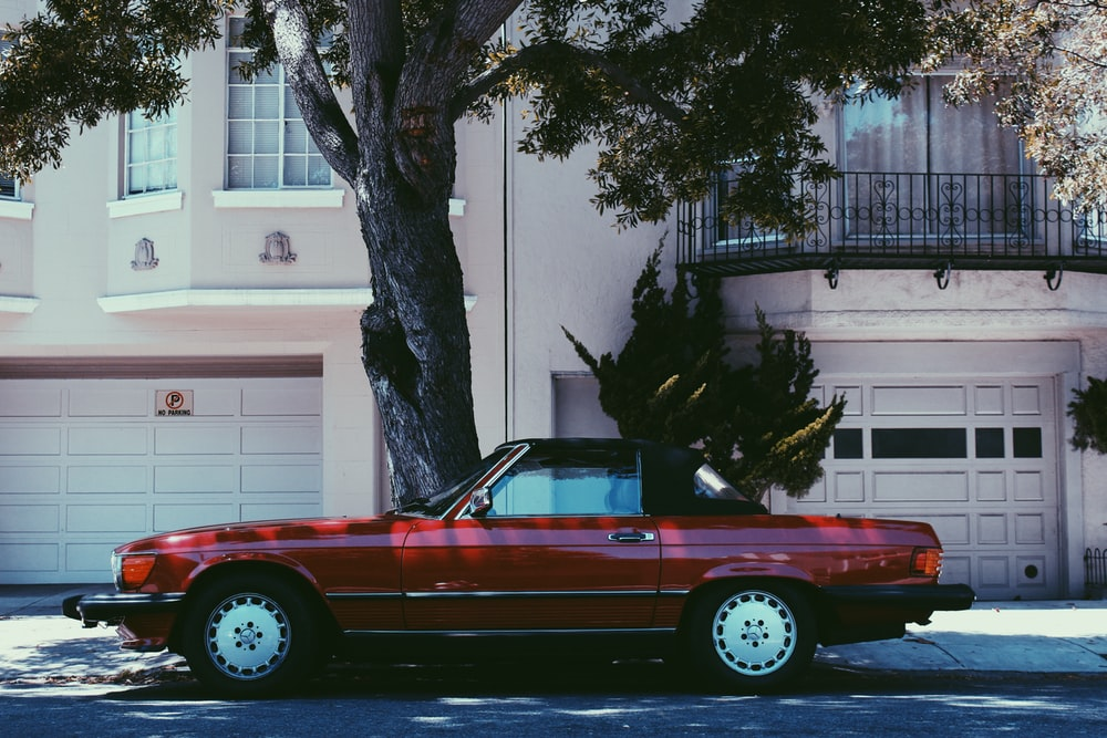 red Mercedes-Benz SLC 45 parked beside tree