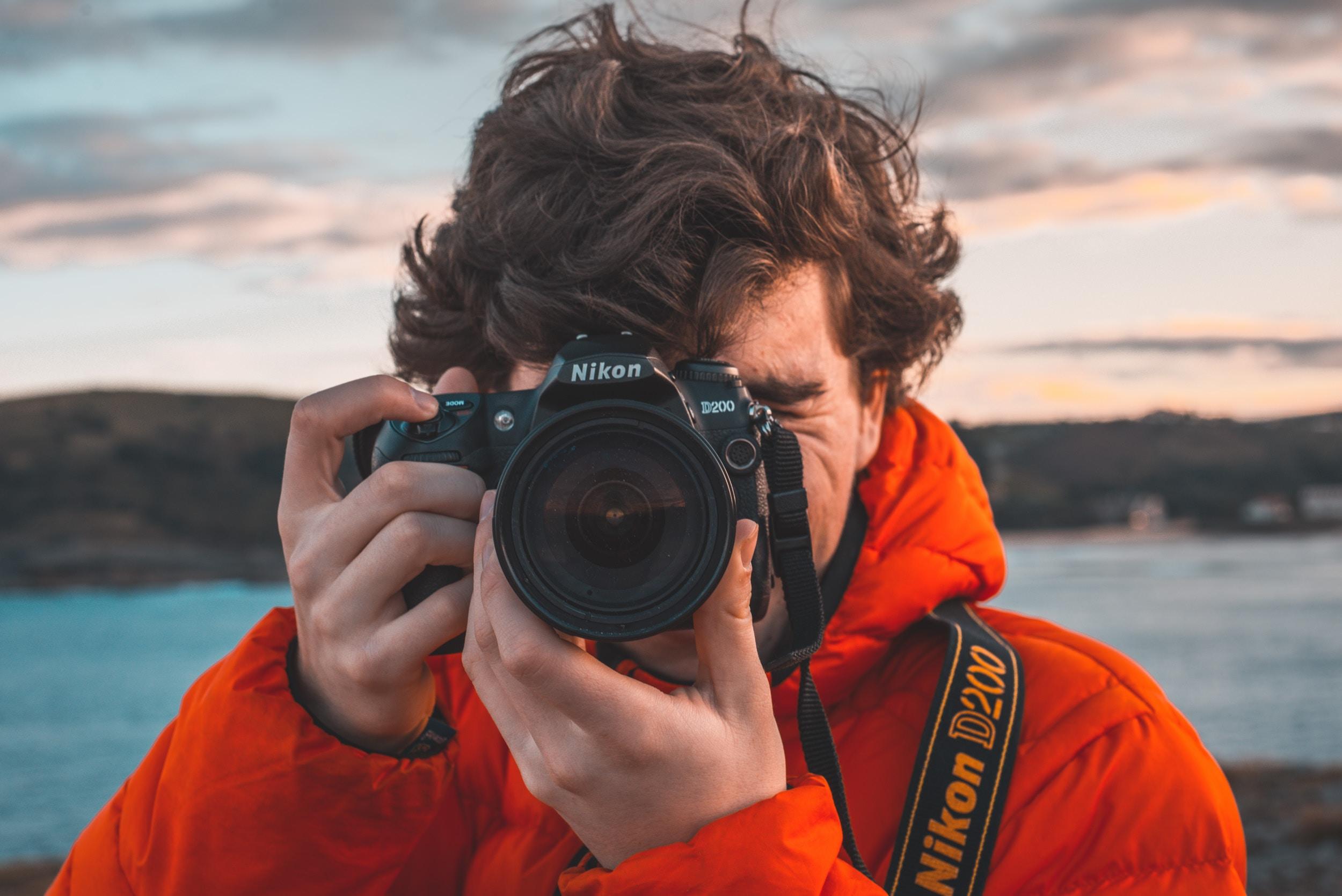 man taking a picture using black Nikon camera