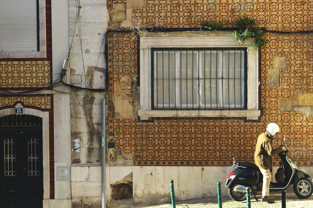 man riding motorcycle beside building during day