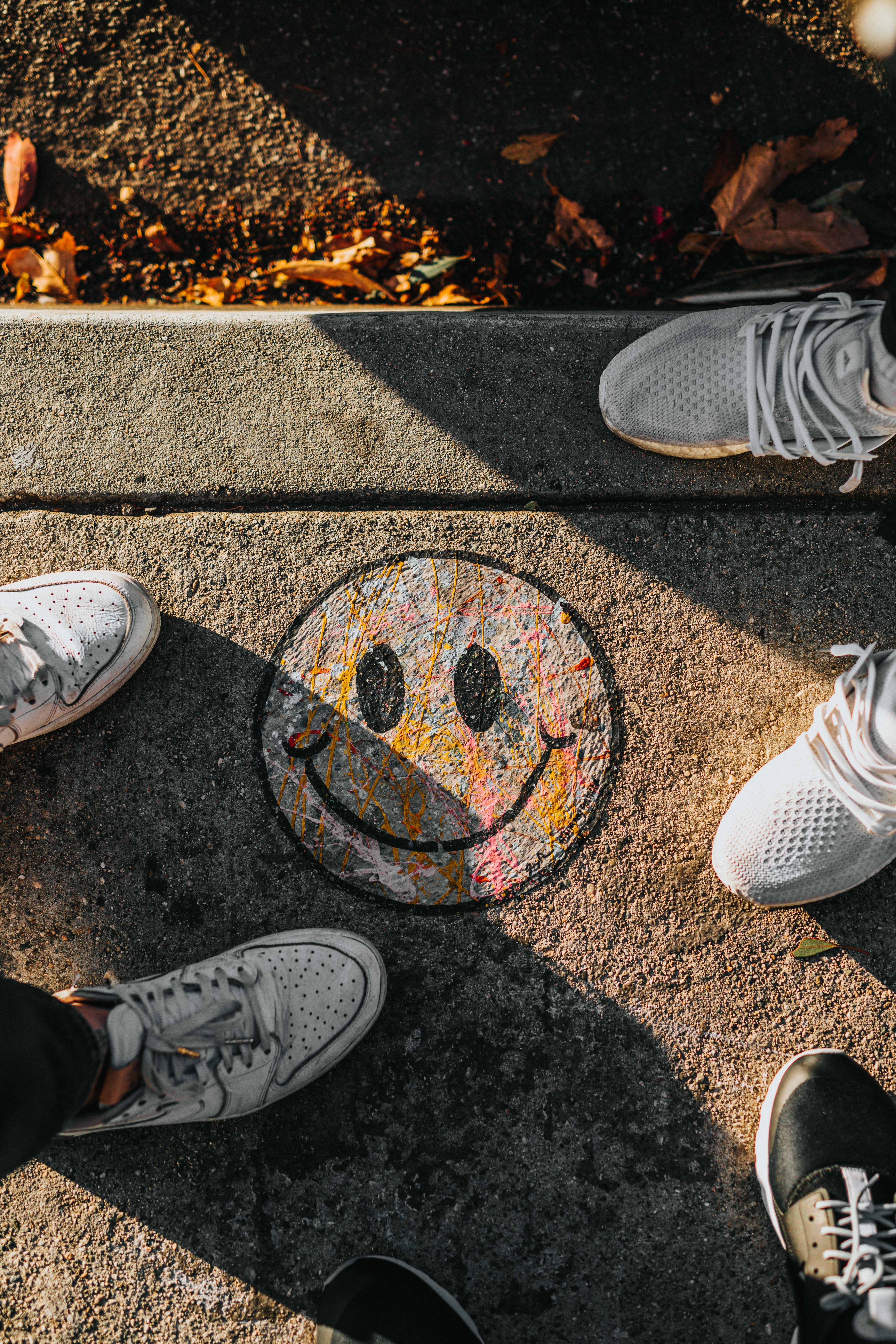 smiley paint on gray ground in front of people