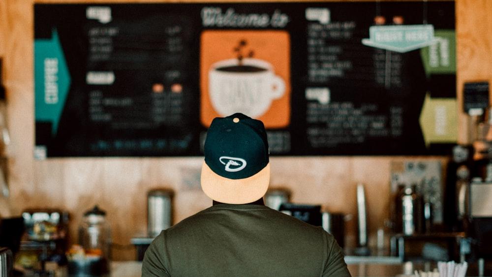 photo of person wearing cap staring at menu board