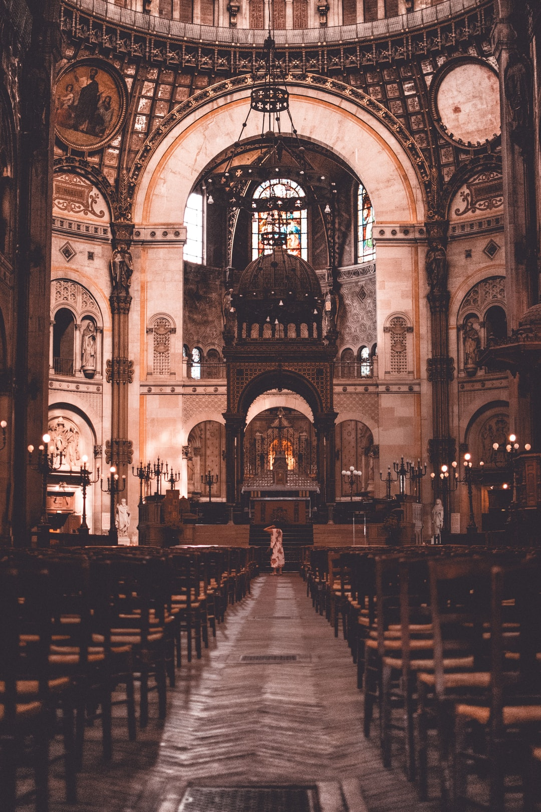 I was visiting a cathedral in Paris, and because the front was undergoing renovations, there were few people around. The only person at the other end of the cathedral was standing in the isle, looking up, a perfect photo opportunity.