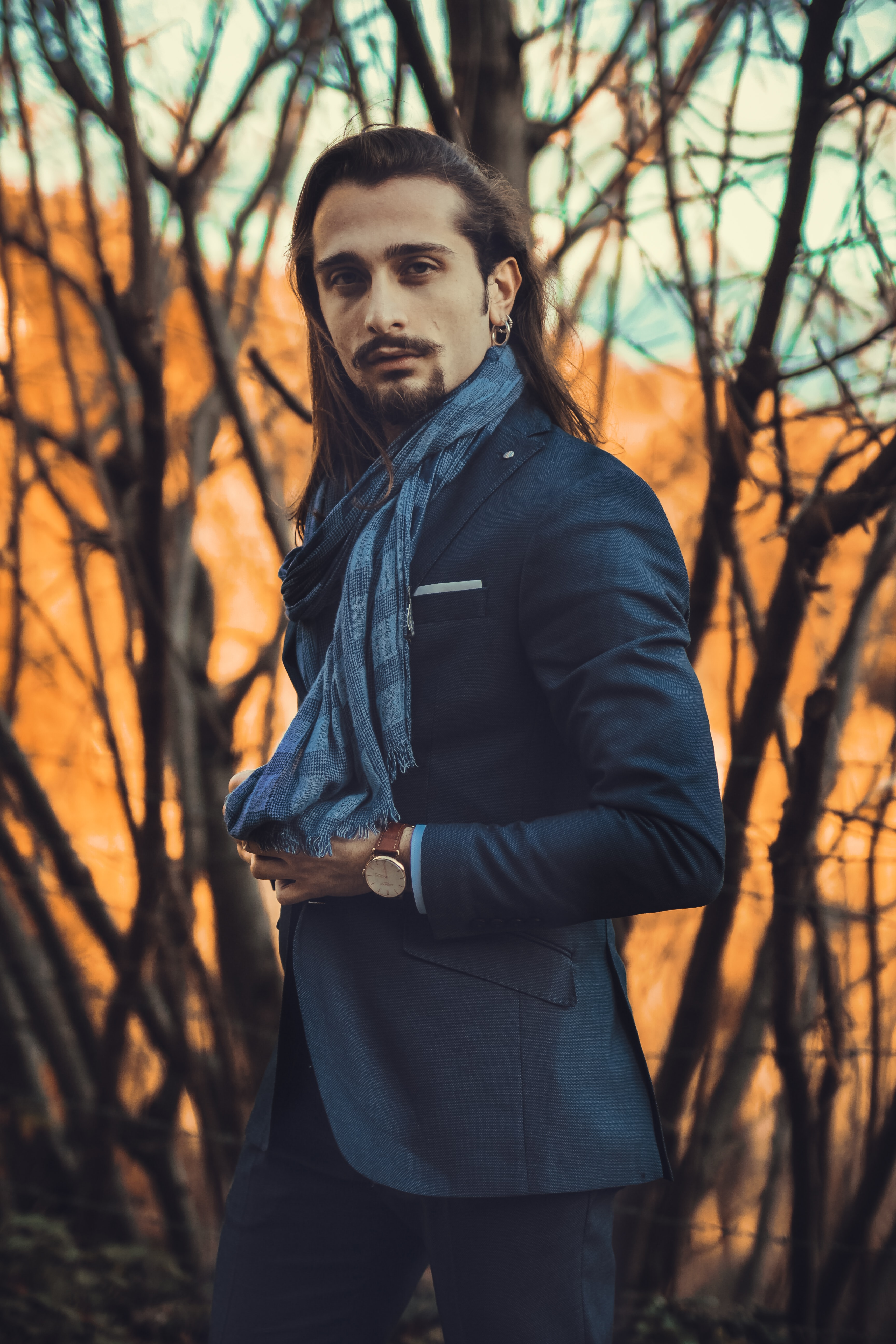 man wearing blue scarf and suit jacket