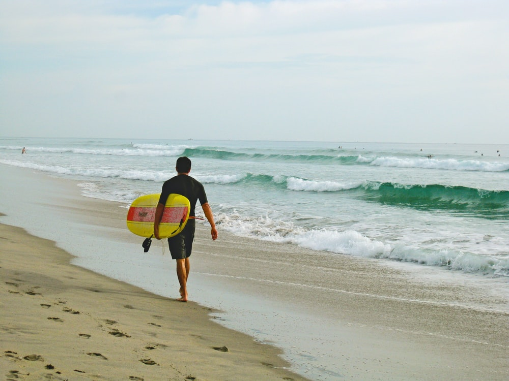 man carrying surfboard while walking on shore