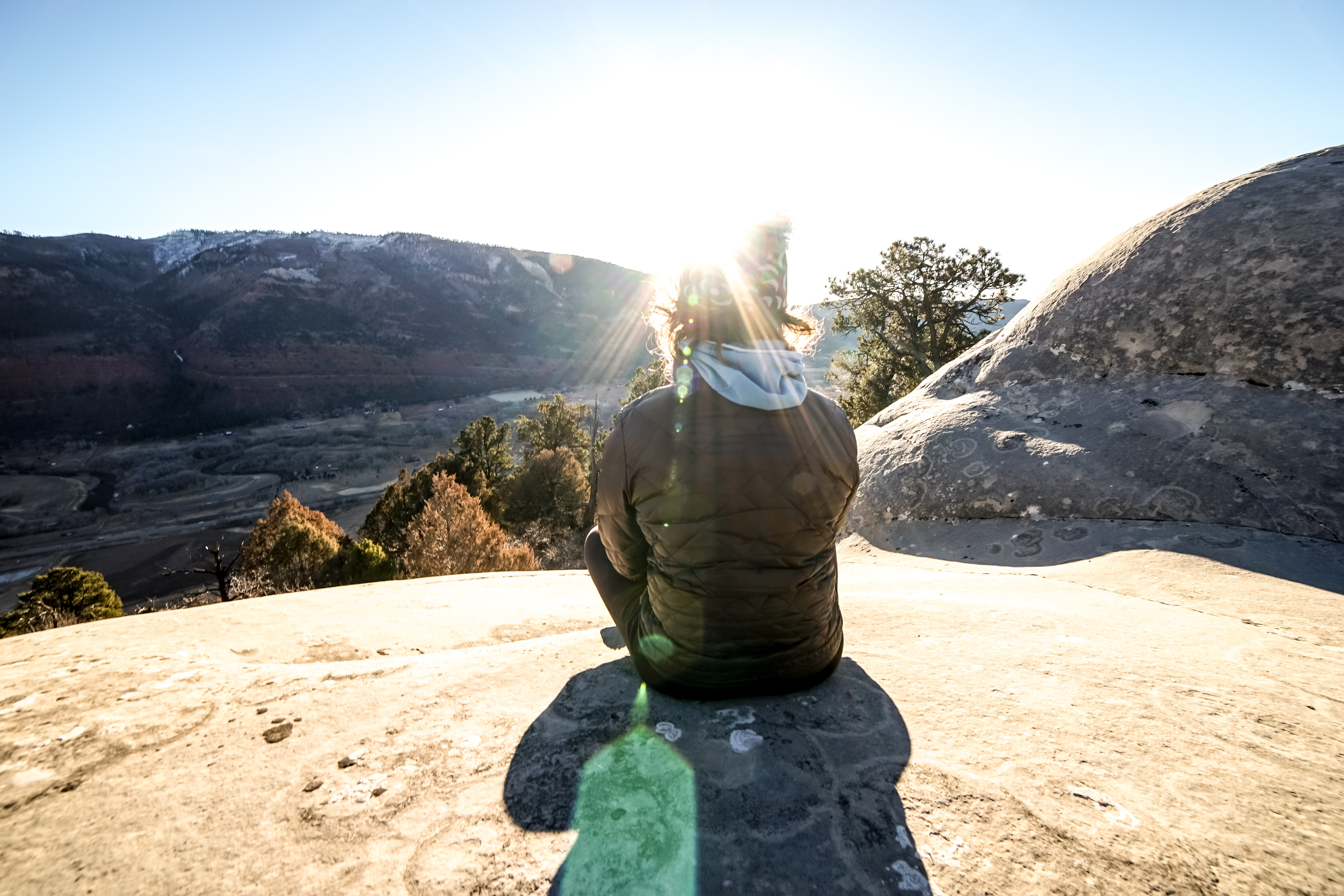 person sitting on top of mountain