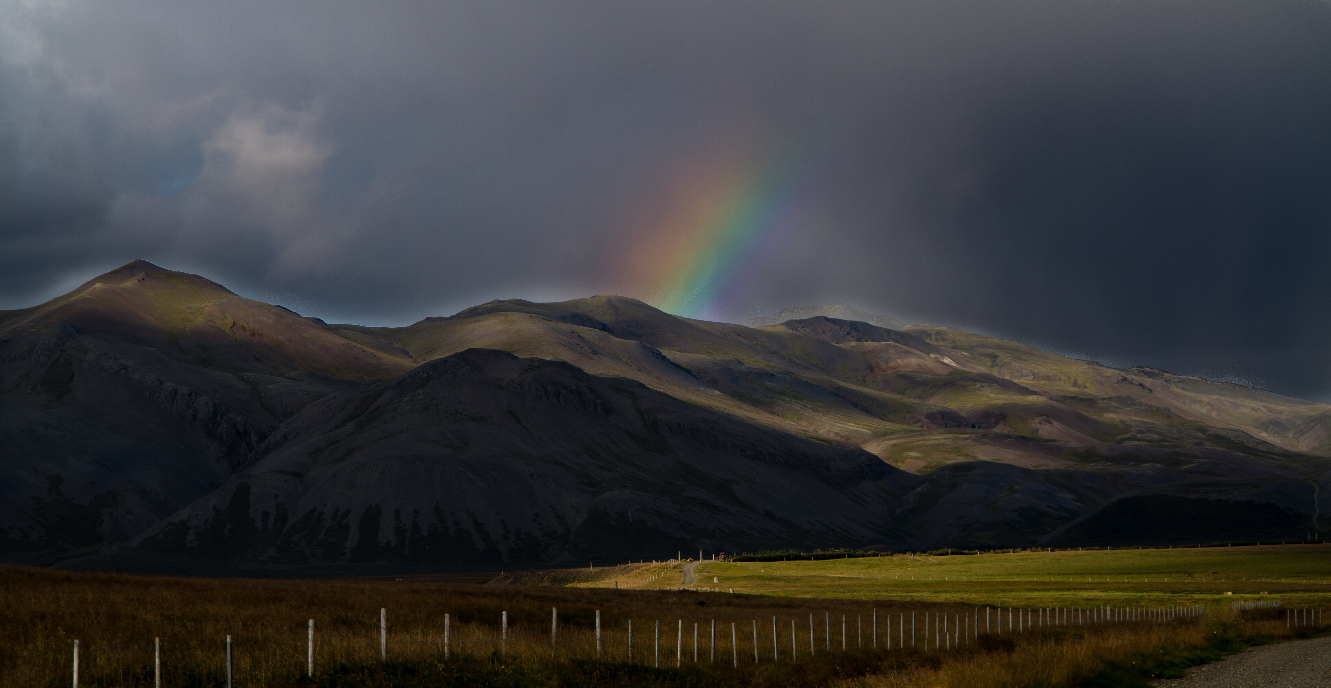 photo of green mountains and rainbow