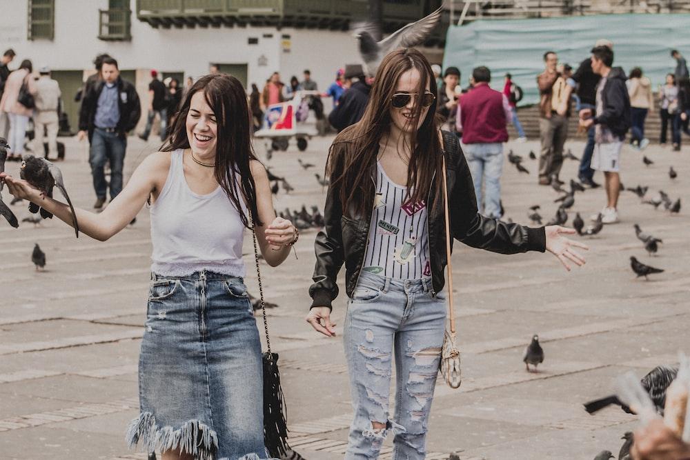 two women standing near pigeons