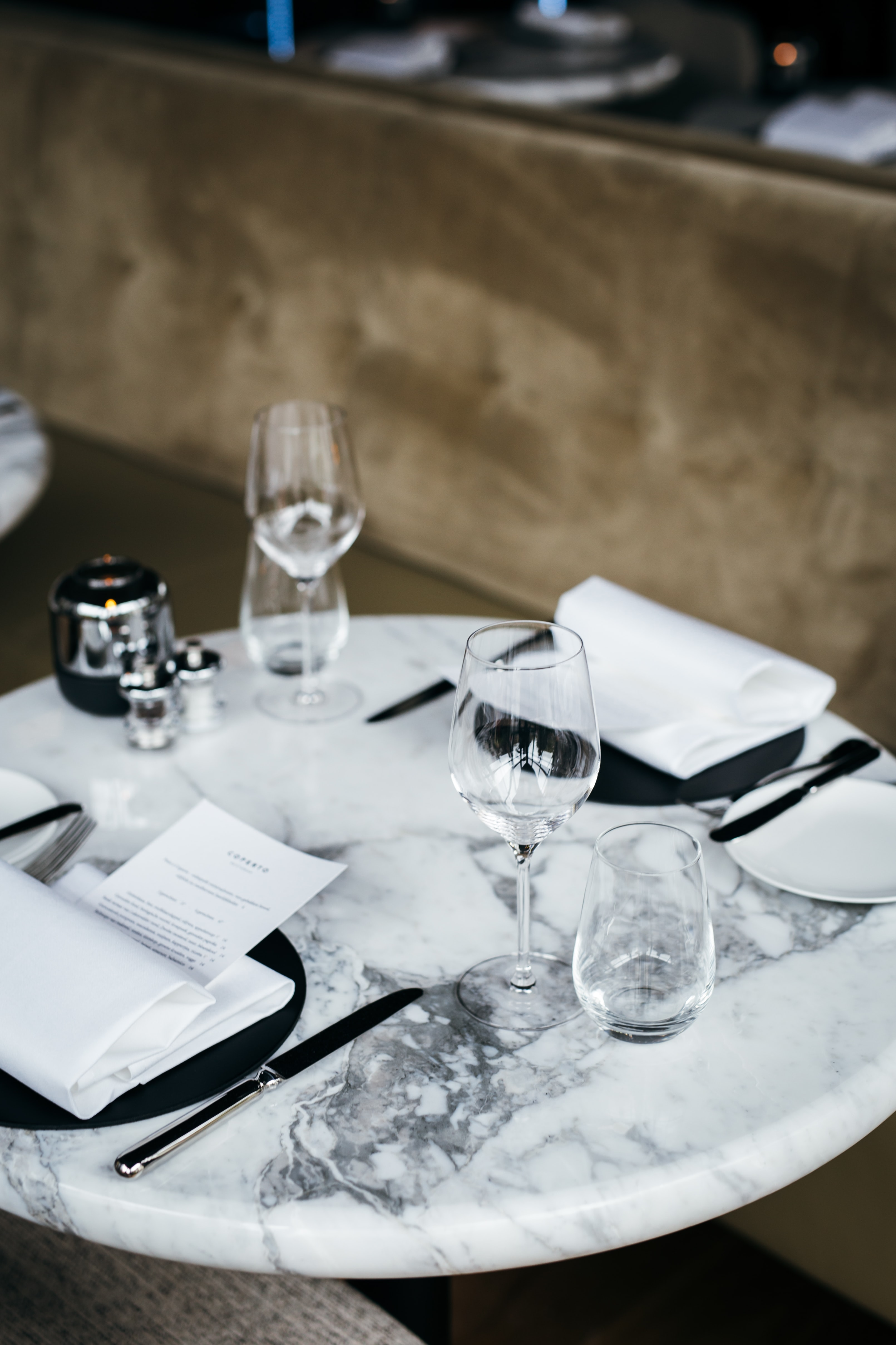 four clear drinking glasses on top of round white marble table