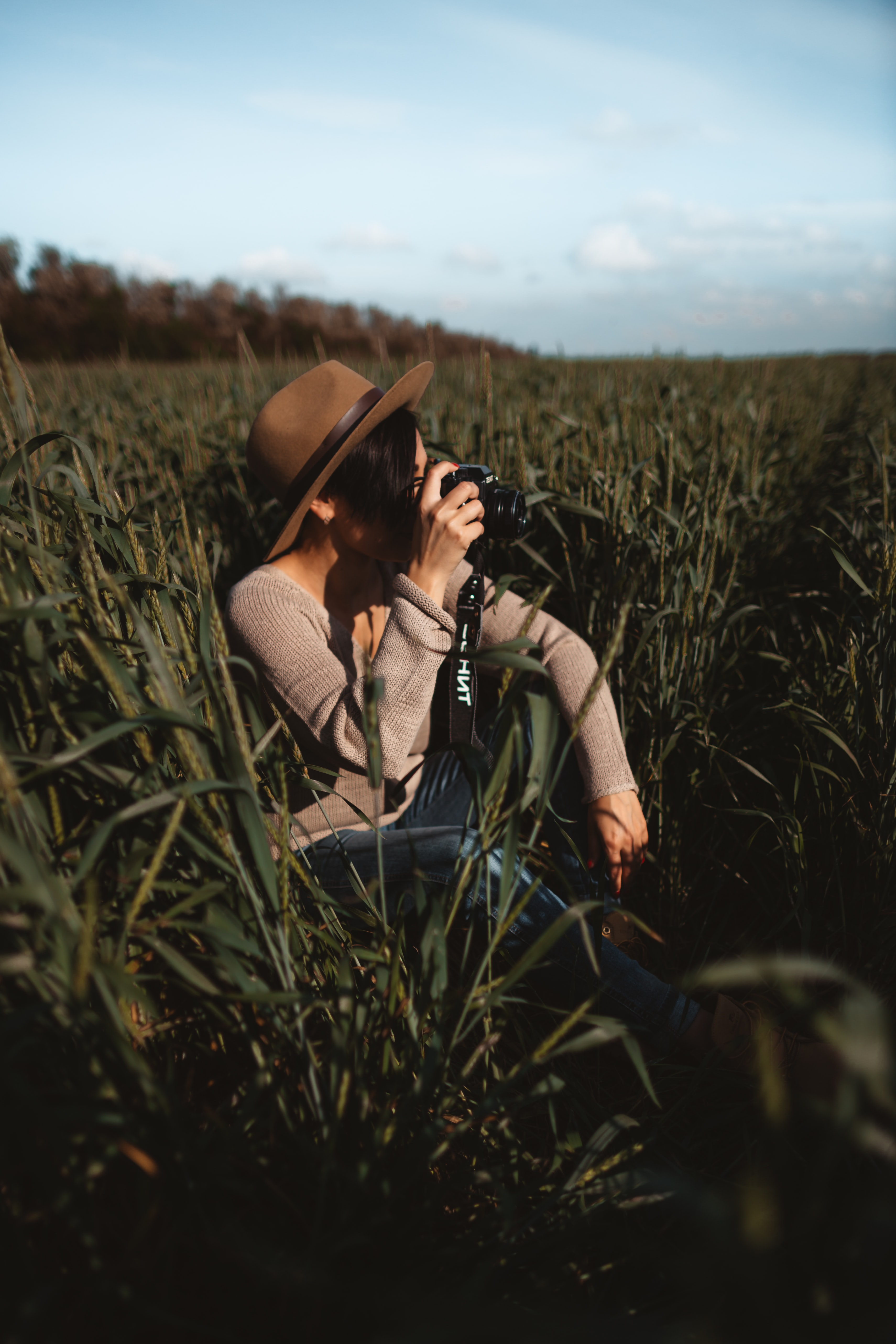 woman taking photo while sitting on green grass field