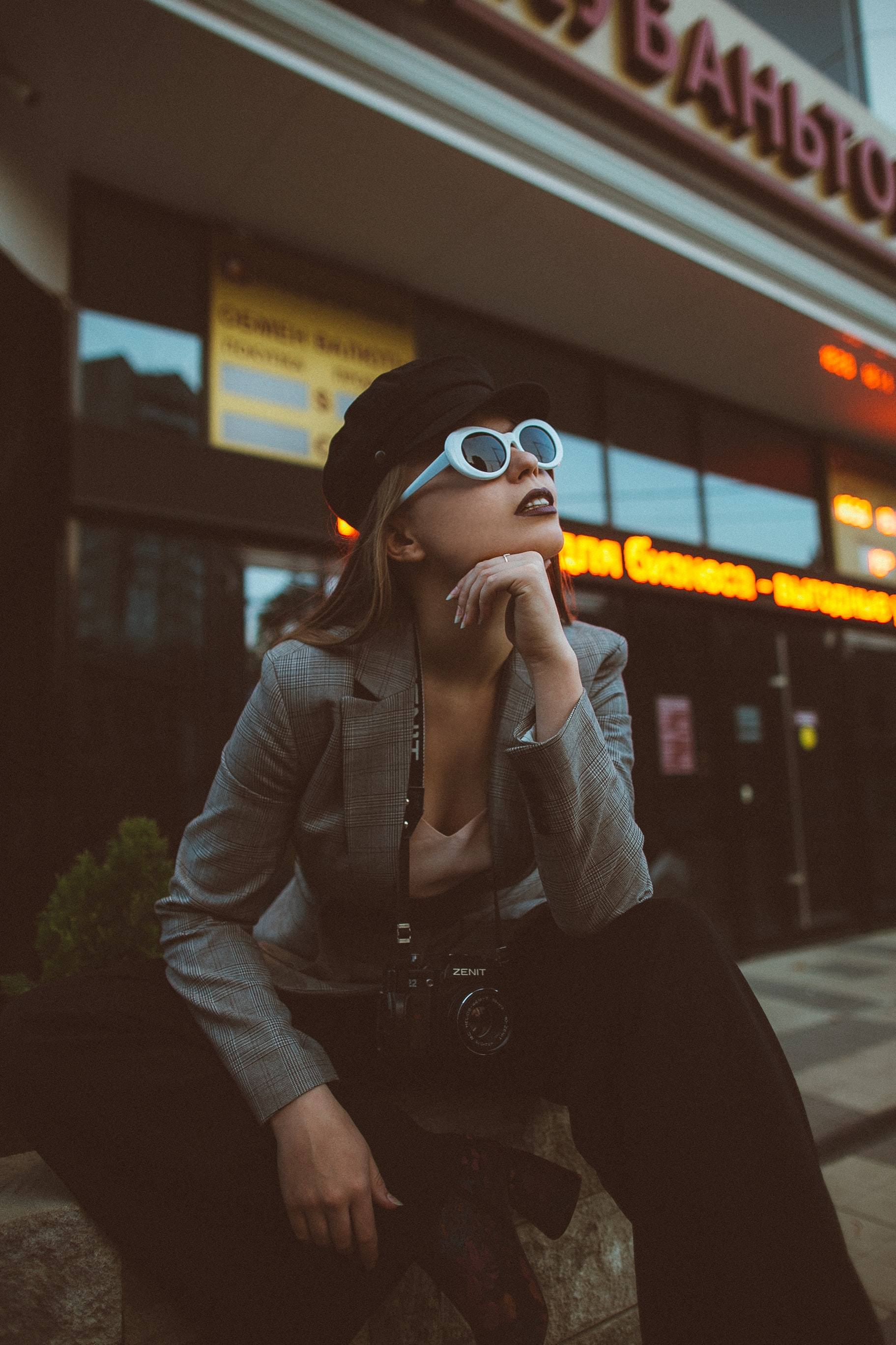 woman wearing sunglasses and sitting on rock