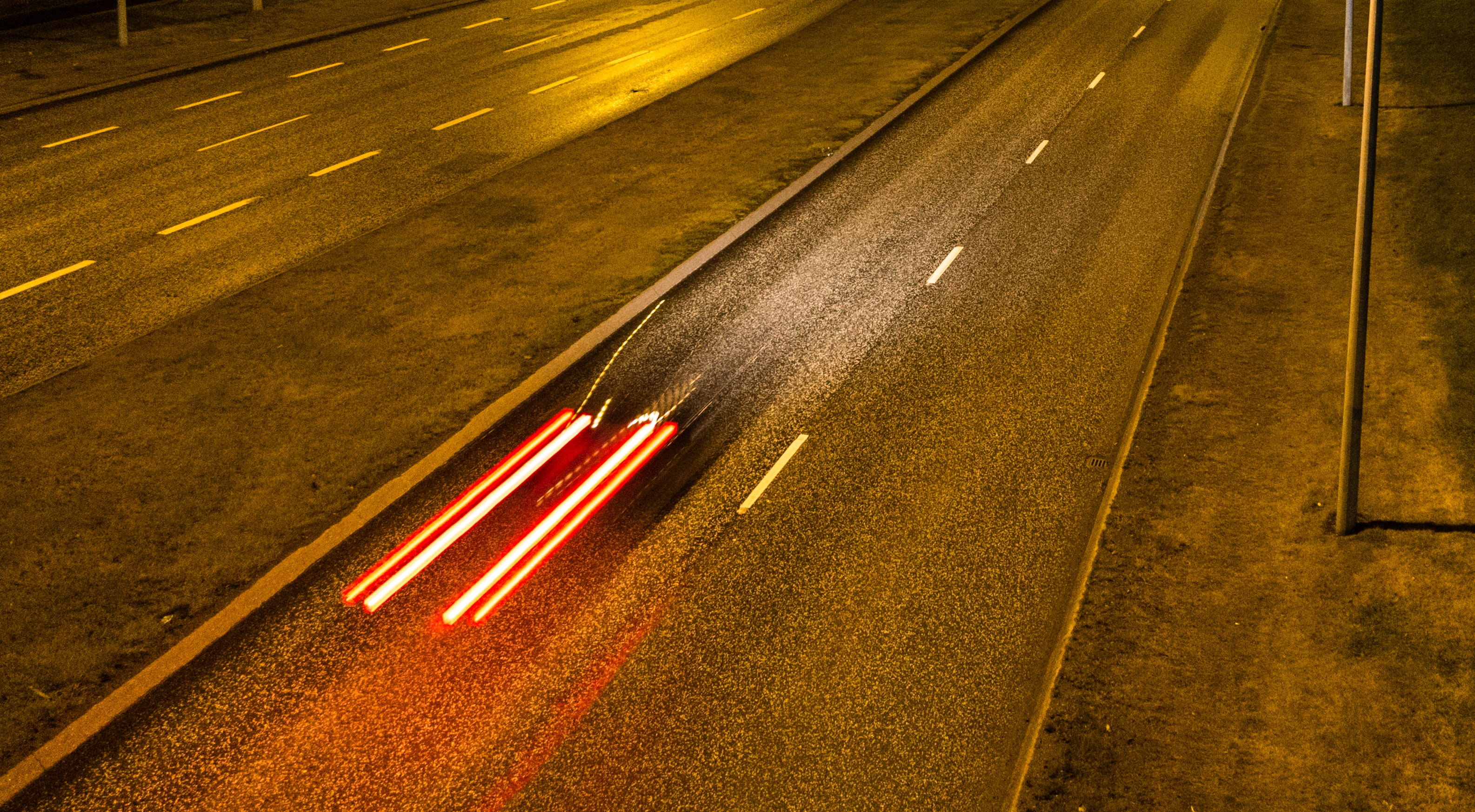panning photo of vehicle traveling on concrete road