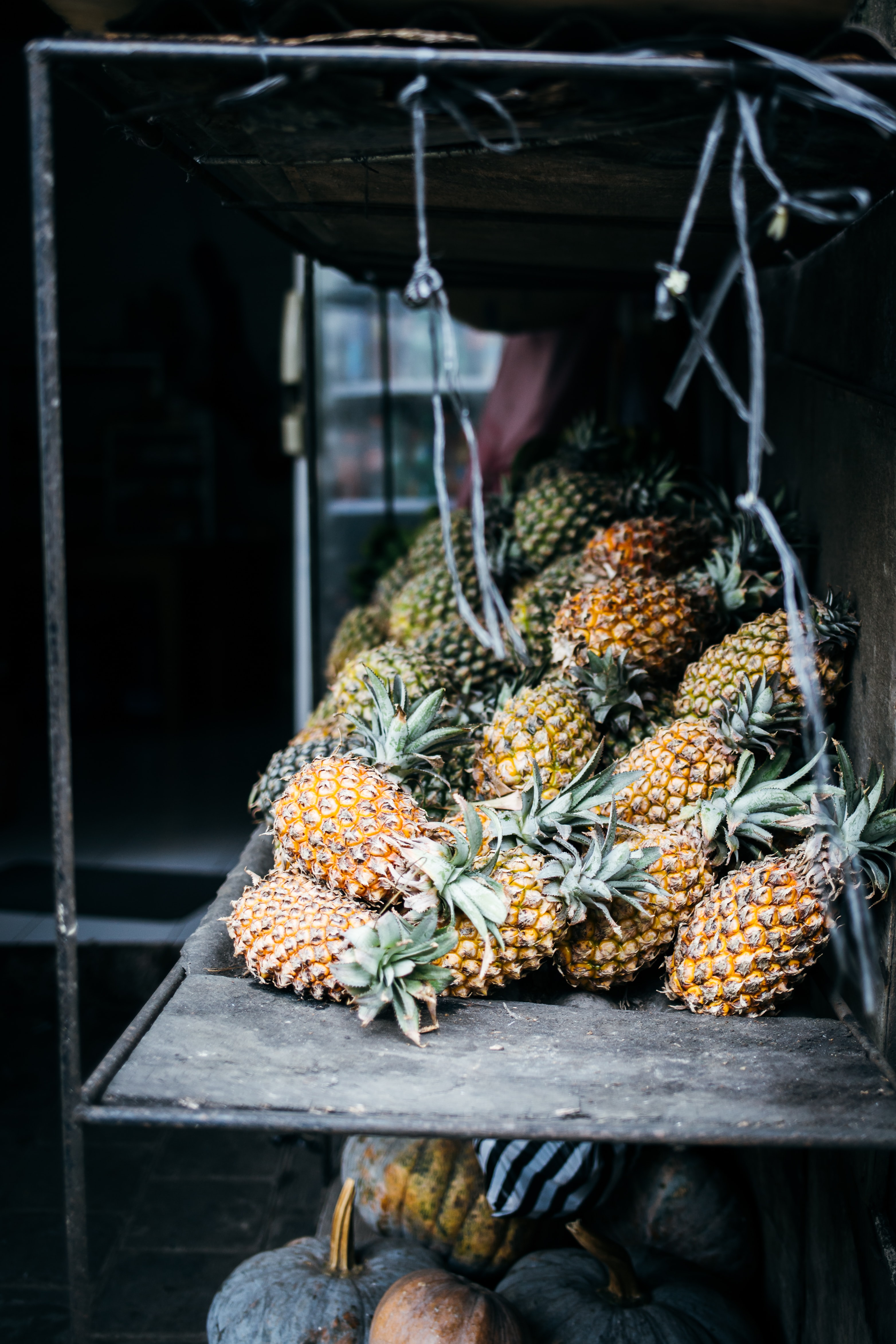 low light photography of pineapples on wooden rack