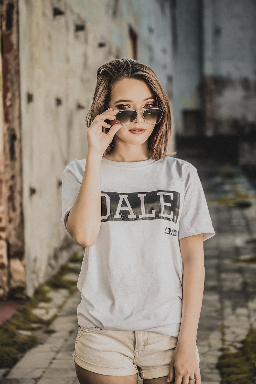 woman in white top holding sunglasses