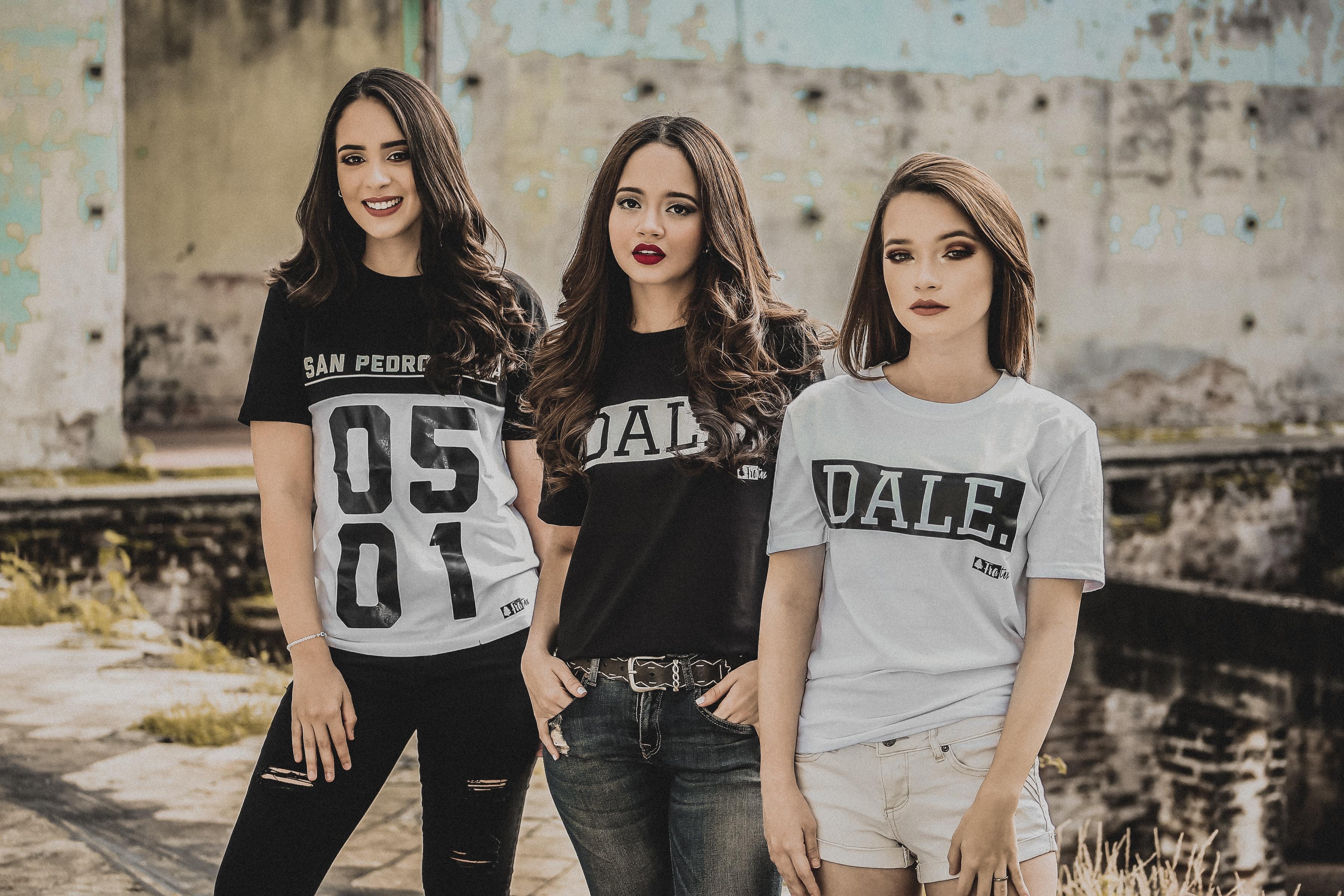 three woman posing near wall