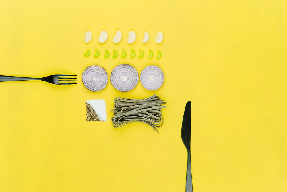 bread knife and sliced onion on yellow table