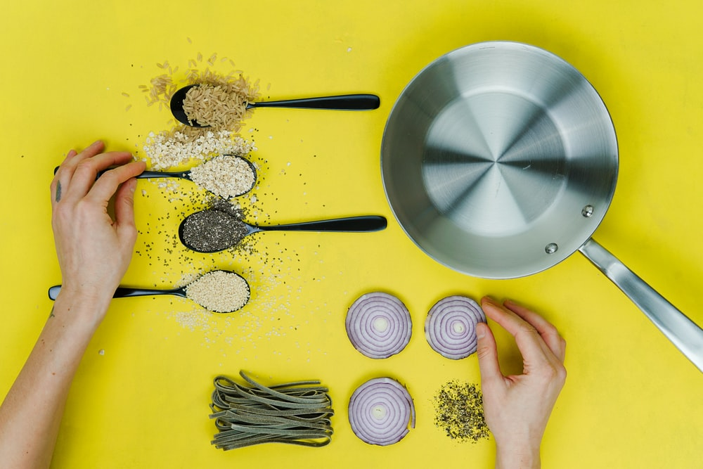 flat lay photography of saute skillet beside spoon of spices and vegetables