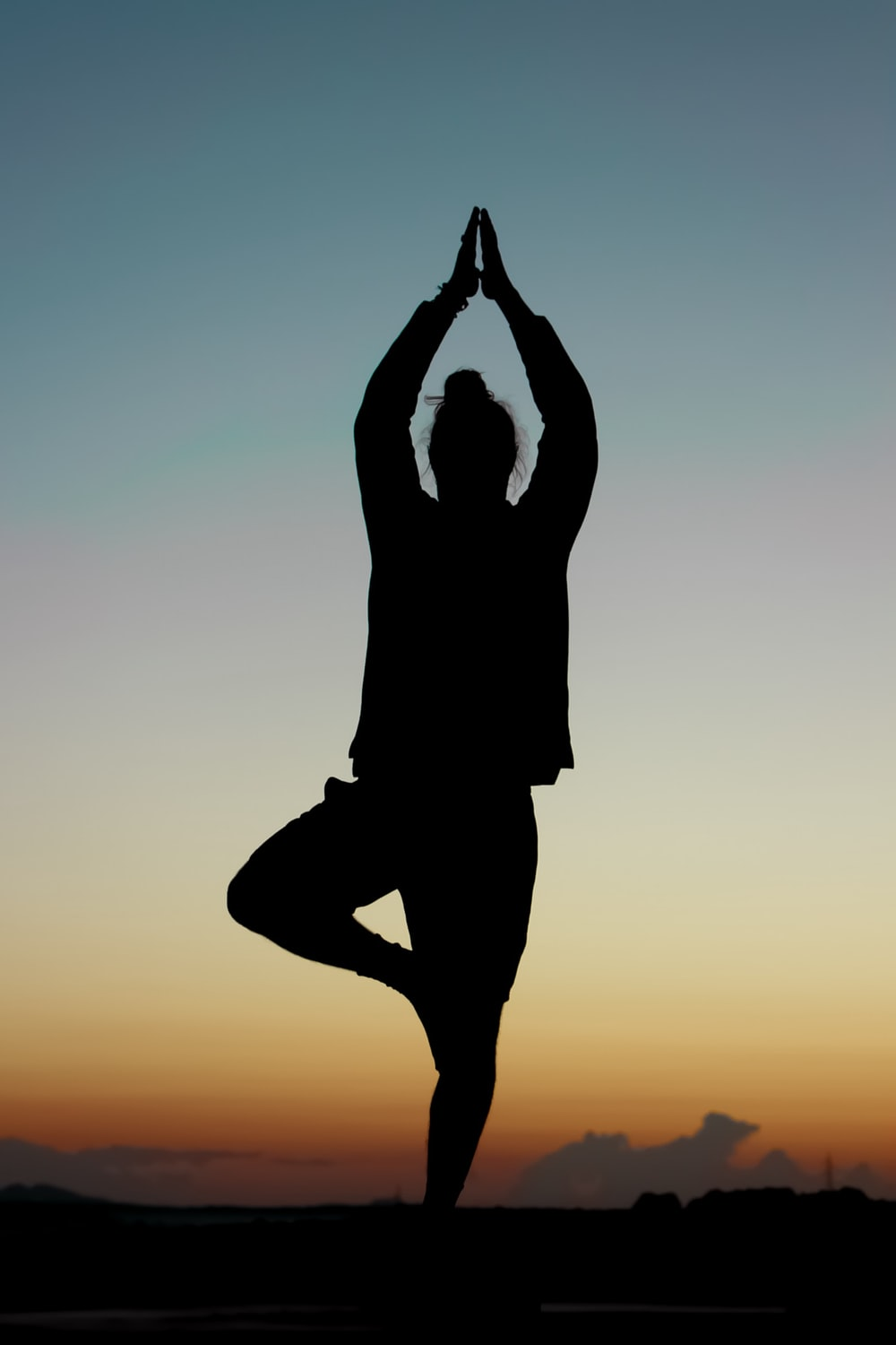 silhouette of person performing yoga