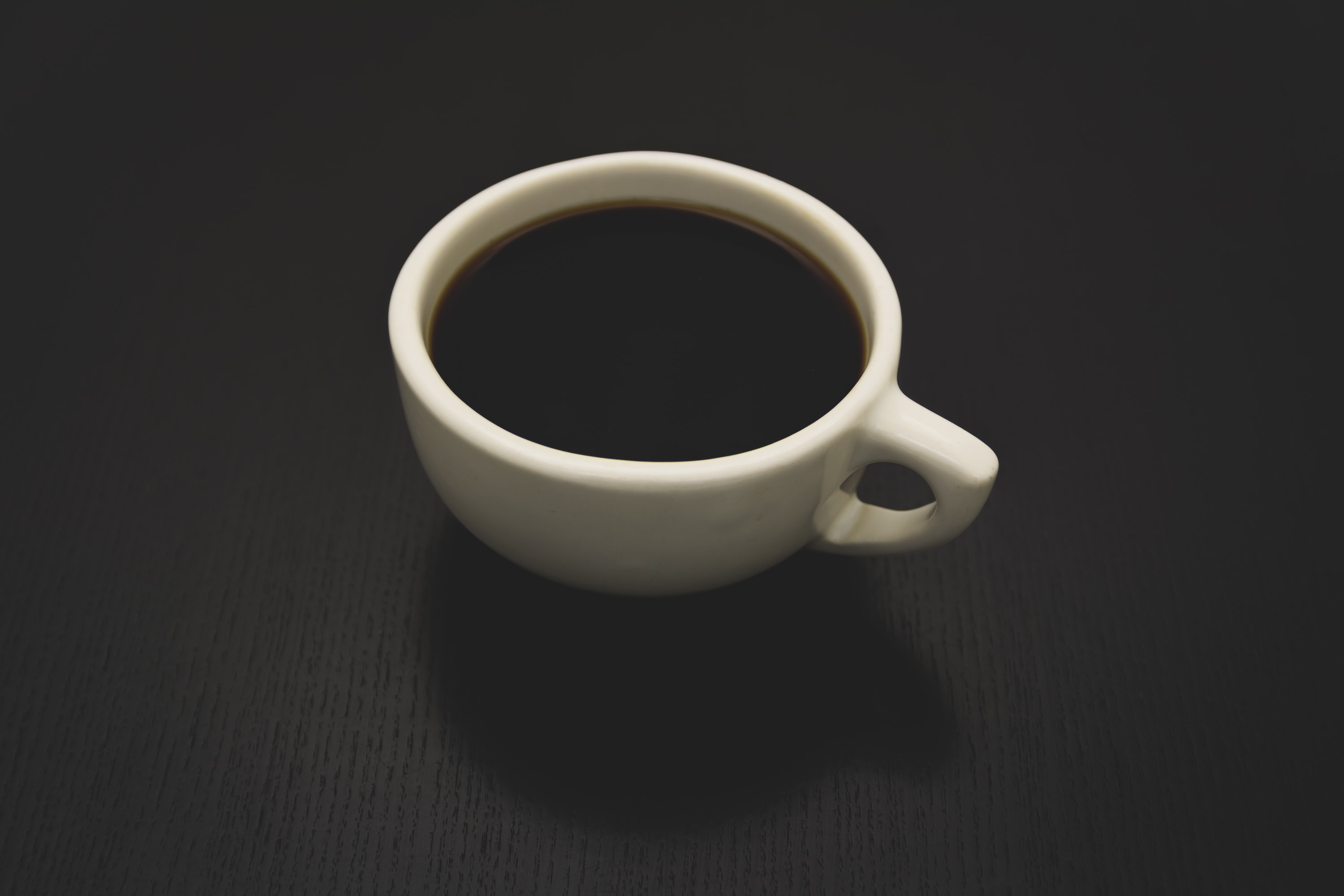 photo of white ceramic teacup filled with liquid