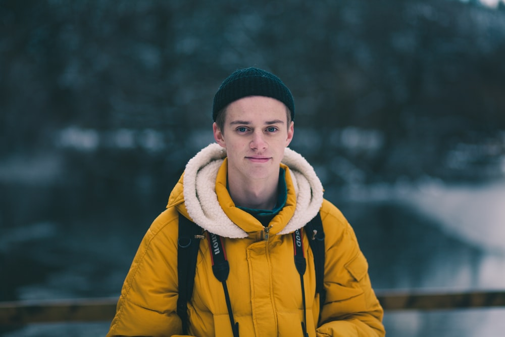 selective focus photograph of man in yellow jacket