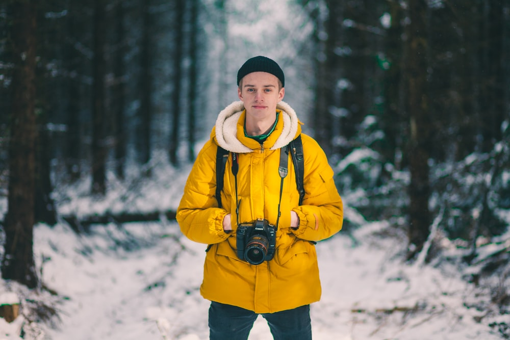 selective focus photo of man standing holding DSLR camera