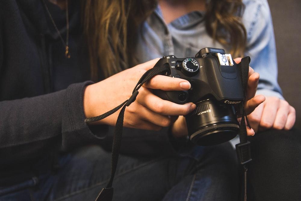 woman holding Canon DSRL camera