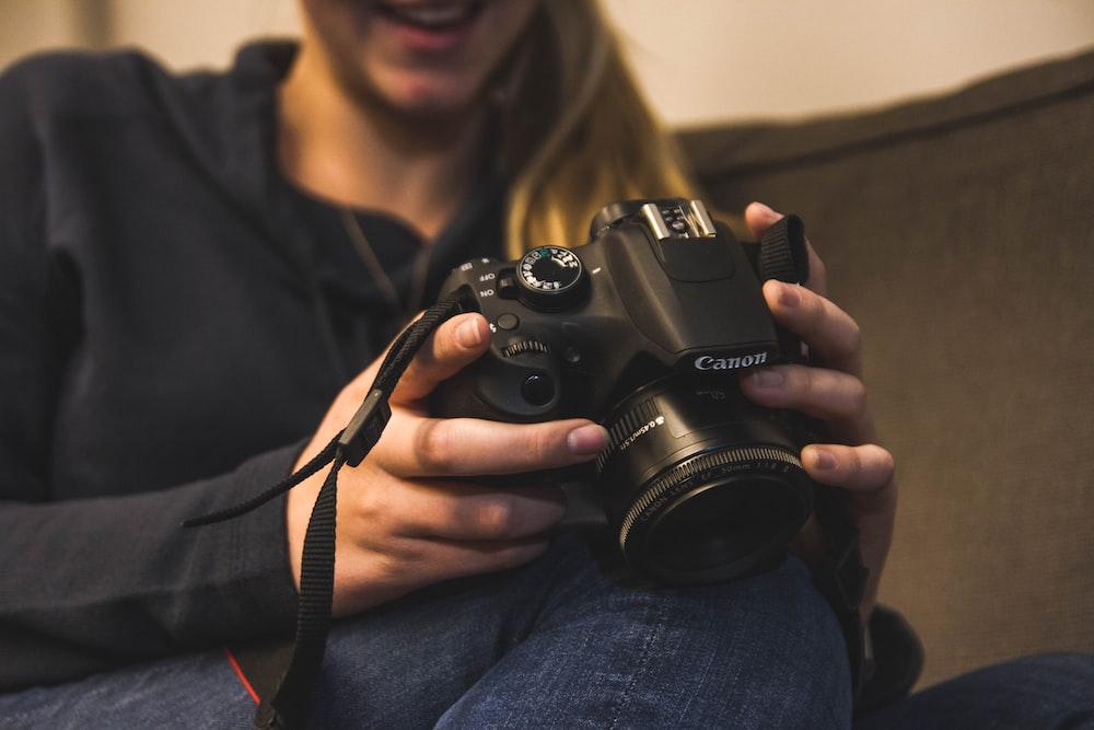 woman holding Canon bridge camera