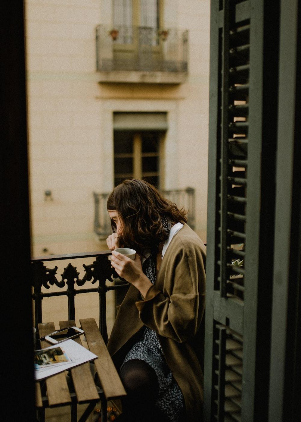 woman drinking white sitting on bench