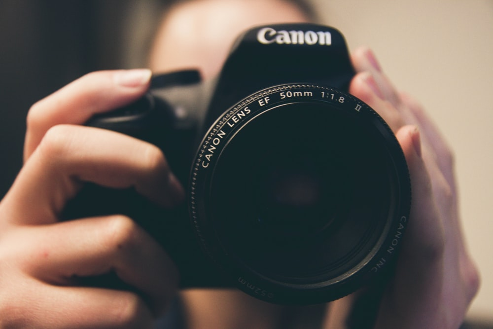 shallow focus photography of person taking photo using Canon DSLR camera