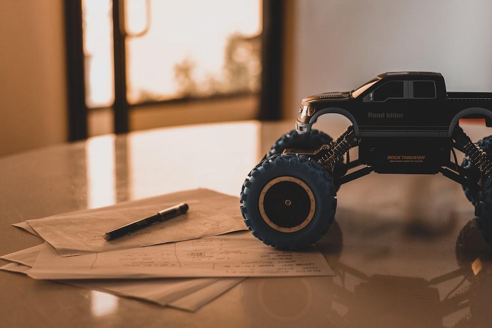 black monster truck toy on white wooden table