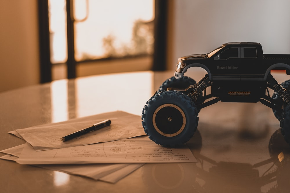 black monster truck toy on white wooden table